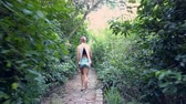 šortky : backside view girl with long plait in blouse and denim shorts walks along abandoned stone path through thickets Dostupné videozáznamy