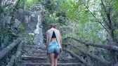 back low angle shot tired girl in denim shorts goes up stone steps with wooden handrail on hill 動画素材
