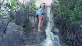 low angle shot tired young woman in denim shorts goes up stone stairs holding wooden railing