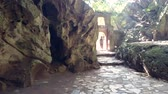 каменная стена : distant young woman enters cave through stone arch gate against sunlight passes rocky walls approaching camera