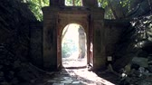 camera removes from ancient stone arch with metal gate and sacral symbols brightly lit by morning sunlight