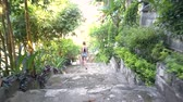 camera follows blond girl with long plait walking down wide beautiful stone track with bench among tropical park