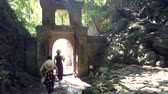 DANANGVIETNAM - MAY 05 2018: Backside view women tourists in straw hats leave cave through gate in stone arch against sunlight in park on May 05 in Danang