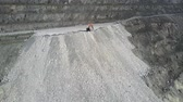 ipuçları : aerial view modern tipper truck pours ground from body on steep grey asbestos pit hill in morning