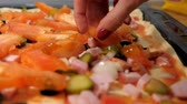 closeup slow motion girl hand with red manicure puts tomato pieces on tasty pizza with beckon and vegetables