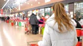 точка зрения : backside view blond girl with ponytail in grey jacket with products in cart walks to free cashier desk in store