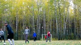 TYUMENRUSSIA - OCTOBER 07 2018: Athletic guys in different clothes play football on sports playground field against yellow birches in park on October 07 in Tyumen Vídeos