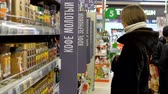 TYUMENRUSSIA - DECEMBER 21 2018: Young blond long haired woman in fur coat with hood chooses coffee jar on selves in modern supermarket on December 21 in Tyumen