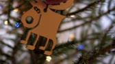 оленьи рога : slow motion close view woman hands hang wooden toy moose on thin christmas tree branch against flashing garland