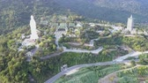 localizar : pictorial aerial view houses with green roofs between white buddha statue and pagoda at dense green forest in Vietnam Archivo de Video