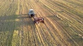 coletor : drone follows tractor and square baler pushes up collected straw bale on harvested field at sunset in autumn