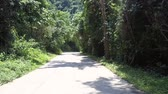 дорожный знак : exciting brown meandering road with red sign between green trees on summer windy day in Vietnam