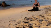meditare : beautiful brunette in black dressing sits on yellow sandy beach meditating with prayer near ocean slow motion. Concept spiritual practices wellness lifestyle teacher guru