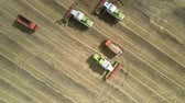 maravilha : TYUMENRUSSIA - AUGUST 31 2018: Wonderful vertical aerial view modern harvesters stand on yellow field and driver runs to loaded orange truck on August 31 in Tyumen