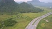 덮개 : flight over valley to hills covered with tropical forest above wide asphalt road crossing boundless fields aerial view