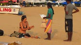 kum saati : MIRISASRI LANKA - APRIL 01 2019: Young tanned european tourist with sunglasses on head sits on beach watching thing from brown local vendor slow motion on April 01 in Mirisa Stok Video
