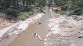 グリット : complicated sand extracting machine works on narrow muddy river surface running among green forest bird eye view. Concept environmental imbalances and illegal sand mining 動画素材