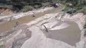 pedreira : long thin pipe extracts wet sand from narrow muddy river bottom into small quarry among green forest aerial view, Concept riverbed destruction and illegal sand mining