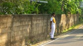 дорожный знак : ColomboSRI LANKA - APRIL 05 2019: Sinhalese schoolboy stands at grey asphalt road holding small sign in hand on sunny day slow motion. Concept system of education on April 05 in Colombo Стоковые видеозаписи