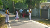 дорожный знак : ColomboSRI LANKA - APRIL 05 2019: Schoolboys help young girl in crossing road on way to school and stop transport with signs slow motion. Concept system of education on April 05 in Colombo Стоковые видеозаписи