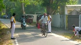 дорожный знак : ColomboSRI LANKA - APRIL 05 2019: Schoolboys in white yellow uniform stand on crossing edges and allow transport to move slow motion. Concept system of education on April 05 in Colombo
