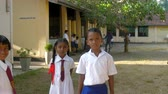 schoolplein : ColomboSRI LANKA - APRIL 05 2019: Sinhalese schoolchildren on schoolyard lit by bright autumn sun against school building slow motion. Concept system of education on April 05 in Colombo Stockvideo