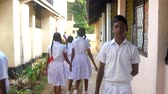 schoolplein : ColomboSRI LANKA - APRIL 05 2019: Sinhalese boys and girls in uniforms walk along thin road between school buildings slow motion. Concept system of education on April 05 in Colombo