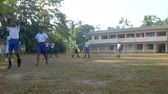 schoolplein : ColomboSRI LANKA - APRIL 05 2019: Sinhalese schoolboys in white shirts and blue shorts walk along green schoolyard slow motion. Concept sport and competition on April 05 in Colombo