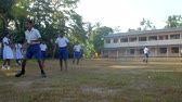 schoolplein : ColomboSRI LANKA - APRIL 05 2019: Schoolboys prepare to game and schoolgirls look at players standing in green trees shadows slow motion. Concept sport and competition on April 05 in Colombo