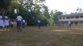 schoolplein : ColomboSRI LANKA - APRIL 05 2019: Schoolboys in white shirts and blue shorts play on green schoolyard against trees slow motion. Concept sport and competition on April 05 in Colombo Stockvideo