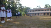 schoolplein : ColomboSRI LANKA - APRIL 05 2019: Sinhalese boys play on schoolyard and girls look against building on sunny autumn day slow motion. Concept sport and competition on April 05 in Colombo Stockvideo