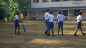 schoolplein : ColomboSRI LANKA - APRIL 05 2019: Sinhalese boys in uniforms prepare for cricket game on playground against school building slow motion. Concept sport and competition on April 05 in Colombo