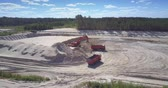 sand pit : TYUMENRUSSIA - JULY 22 2018: Powerful digger loads sand into tipper workbody in developed pit near green forest bird eye view. Concept ecosystem disturbance on July 22 in Tyumen