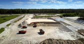 volqueta : TYUMENRUSSIA - JULY 22 2018: Modern digger and tippers with workers operate with sand at large open pit against wood and sky upper view. Concept environmental imbalances on July 22 in Tyumen