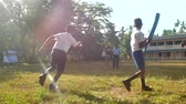 schoolplein : ColomboSRI LANKA - APRIL 05 2019: Active boy in uniform with blue cricket bat throws ball to schoolmate on playground slow motion. Concept sport and competition on April 05 in Colombo Stockvideo