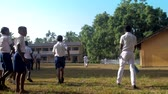 schoolplein : ColomboSRI LANKA - APRIL 05 2019: Guy holds cricket bat near schoolmates walking along green playground slow motion. Concept sport and healthy lifestyle on April 05 in Colombo
