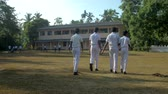 schoolplein : ColomboSRI LANKA - APRIL 05 2019: Schoolboys walk to school building leaving shadows on playground against green trees slow motion backside view. Concept sport and competition on April 05 in Colombo Stockvideo
