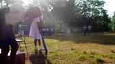 schoolplein : ColomboSRI LANKA - APRIL 05 2019: Young lady in white dress silhouette holds blue cricket bat with funny schoolboy on foreground slow motion. Concept gender equality on April 05 in Colombo Stockvideo