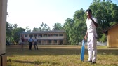 schoolplein : ColomboSRI LANKA - APRIL 05 2019: guy in white dressing shows gestures and turns around holding cricket bat slow motion. Concept sport and healthy lifestyle on April 05 in Colombo