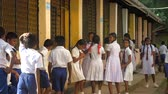 平等 : ColomboSRI LANKA - APRIL 05 2019: Sinhalese schoolkids in uniforms stand at building in school yard waiting for lesson after break slow motion. Concept gender equality on April 05 in Colombo