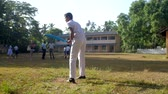 schoolplein : ColomboSRI LANKA - APRIL 05 2019: Sinhalese boy in school uniform prepares for cricket game holding blue bat on green playground slow motion. Concept sport and healthy lifestyle on April 05 in Colombo Stockvideo