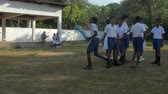 schoolplein : ColomboSRI LANKA - APRIL 05 2019: Young cricket players in school uniform prepare to game on playground in green trees shadows slow motion. Concept sport and competition on April 05 in Colombo