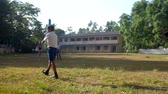 schoolplein : ColomboSRI LANKA - APRIL 05 2019: Young Sinhalese pupil walks along green playground grass holding cricket bat against school slow motion. Concept sport and competition on April 05 in Colombo