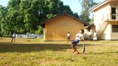 schoolplein : ColomboSRI LANKA - APRIL 05 2019: Barefoot schoolboy in blue shorts and white shirt bats cricket ball on playground slow motion backside view. Concept sport and competition on April 05 in Colombo Stockvideo