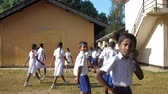 平等 : ColomboSRI LANKA - APRIL 05 2019: Sinhalese schoolchildren return to classes after break on open air slow motion backside view. Concept gender equality and healthy lifestyle on April 05 in Colombo