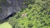 iszapos : old Buddhist temple on green mountain hill at large cave and muddy running river on sunny day upper view