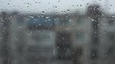 Drops of rain on a window pane, buildings in background.