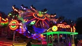 wesołe miasteczko : BERLIN, Germany - JUNE 3, 2017: Funfair Ride (Flea Market) Flipper at German Fun Fair (Fair) at night - Wide Shot - 4K