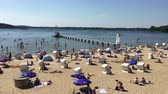 kayıtlar : Berlin, Germany - May 29 2018: Pan over people enjoying the sun and beach at Wannsee in hot weather