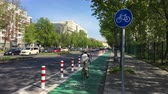 дорожный знак : BERLIN - APRIL 20, 2019: New Protected Bike Lane in Berlin - Cyclist and car passing by Стоковые видеозаписи